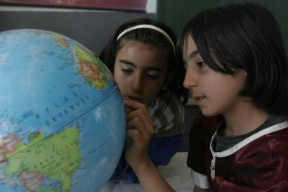 (Right) Yaprak, 10, and a classmate examine a globe at their school in the village of Karaali in Ankara Province. Today is the last day of school and Yaprak is wearing a red velvet dress to celebrate. The 'child-friendly' school offers a free education to local pupils (all the girls of the village are enrolled), as well as boarders, many of whom are orphans or otherwise at risk. Child-friendly schools promote free, compulsory education for all children in a safe, clean learning environment that respects diversity and the rights of the child. Yaprak's father works for a local landowner in exchange for a house and a small stipend. [#2 IN SEQUENCE OF EIGHT]